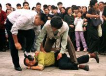 Các cảnh sát mật bắt giữ một học viên Pháp Luân Công trên Quảng trường Thiên An Môn, vào khoảng năm 2000.