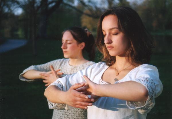"""Hai cô gái người Đức đang quay tay giống như đang xoay một quả cầu – một phần trong bài Công pháp thứ 4 """"Pháp Luân châu thiên pháp"""""""