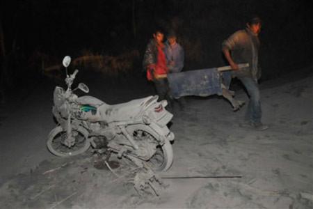 Một nạn nhân của núi lửa Merapi đang được đưa đi trong lớp tro bụi dày. Ảnh: AFP