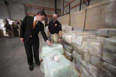 Ông John Morton (trái) đang xem xét các gói ma túy dưới đường hầm hôm 3-11. Ảnh: REUTERS