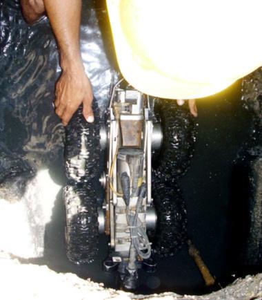 Nhiệm vụ của hai con robot này là kiểm tra hệ thống thoát nước phát hiện những lỗi, khuyết tật như hở múi nối, những mảng bám, rò rỉ... kịp thời báo cáo về Trung tâm điều hành chương trình chống ngập nước TP để có biện pháp khắc phục. Trong ảnh là một công nhân đang cho robot chui vào cống.
