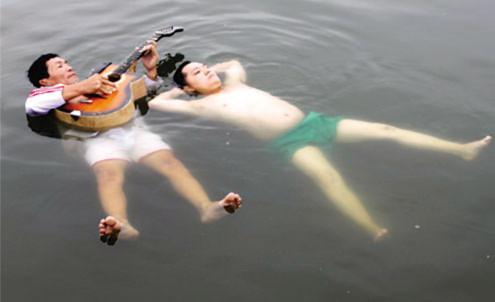 Ông Hứa Văn Bạch (trái) đàn guitar còn ông Hứa Tây Hạ hát vọng cổ trong tư thế thả nổi trên mặt nước gần 4 giờ. Ảnh: Vietkings