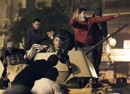 Một nhóm thanh niên chiếm xe bọc thép của quân đội tại Cairo hôm 28/1. Ảnh: AP.