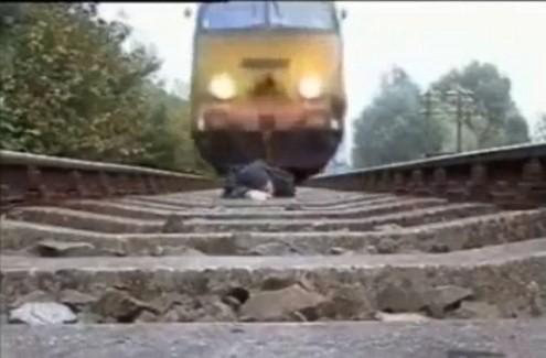 Nằm trên đường ray cho tàu hỏa chạy qua để... biểu diễn - Tin180.com (Ảnh 1)