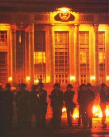 4h sáng, ngày 4/6/1989, Bắc Kinh: Quân lính tràn ra từ Đại Lễ đường Nhân dân, với súng nhắm thẳng vào sinh viên đứng dưới tượng đài Anh hùng. Những người lính khai hỏa trước khi họ tiến tới. Trong bức ảnh, tia sáng lóe lên từ họng súng của một quân nhân được nhìn thấy rất rõ ràng (Đại Kỷ Nguyên)