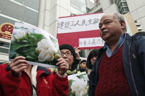 """Người biểu tình giơ cao hình ảnh của hoa nhài để ủng hộ 'Cuộc cách mạng Hoa Nhài"""" ở Trung Ðông bên ngoài các văn phòng liên lạc của Trung Quốc ở Hồng Kông, ngày 20/2/2011"""