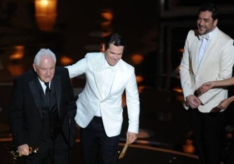 Tài tử No country for old men Javier Bardem (phải) nhìn đồng nghiệp Josh Broslin trao giải Oscar Kịch bản gốc xuất sắc cho David Seidler, biên kịch The King's Speech.