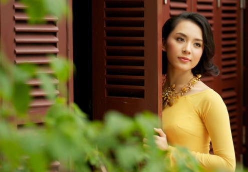 Hình ảnh người đẹp tươi sắc áo vàng thấp thoáng bên khung cửa gỗ gợi hình ảnh xuân về.