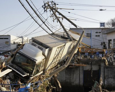 Xe tải bị sóng thần hất tung lên cao.