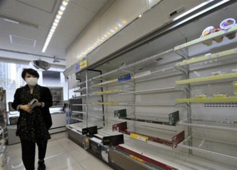 Một phụ nữ đi qua giá đề đồ trống trơn tại một siêu thị ở Tokyo. Ảnh: AFP.