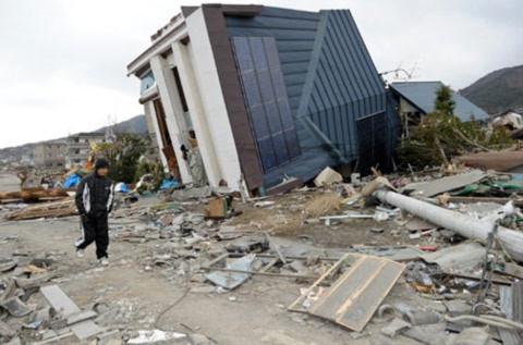 Một người dân Nhật đi qua đống đổ nát và ngôi nhà xiêu vẹo ở thành phố Ofunato,