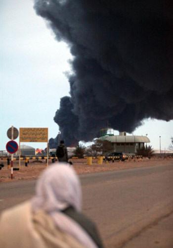 Lửa khói bốc lên từ một nhà máy lọc dầu ở thành phố Ras Lanuf khi quân đội chính phủ giao tranh với phe nổi dậy Libya. Ảnh: AFP