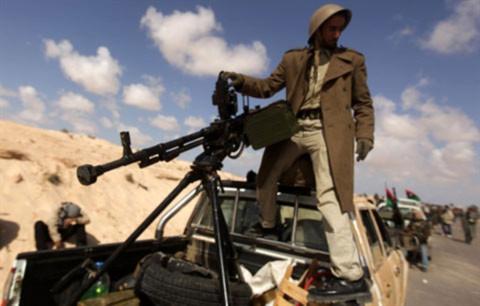 Một thành viên phe nổi dậy chuẩn bị cho cuộc tấn công vào thành phố Ajdabiya. Ảnh: AFP.