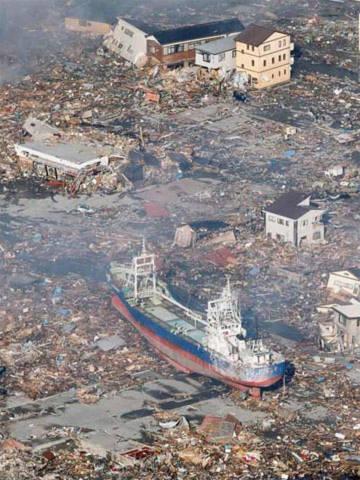 Một con tàu lớn bị sóng thần hất văng lên đường phố bên những ngôi nhà đổ nát ở thành phố Kasennuma. Ảnh