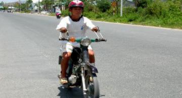 Cụt hai tay vẫn đi xe máy chở con đến trường