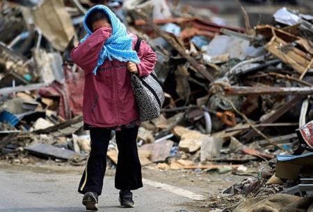 Một phụ nữ Nhật gạt nước mắt khi đi qua đống đổ nát sau trận sóng thần. Ảnh: AP.