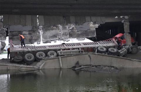 Chiếc xe nằm đổ gãy dưới gầm cầu. Cả hai người trên xe bị thương.