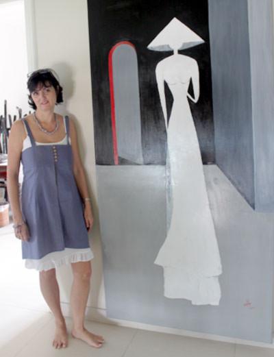Helene Kling bên một bức họa thiếu nữ mặc áo dài, đề tài yêu thích của chị.