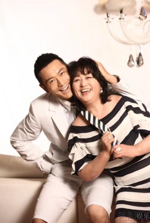 """Lúc người mẹ đang được trang điểm để chuẩn bị cho buổi chụp ảnh, Huỳnh Hiểu Minh luôn đứng cạnh mẹ, ngắm nhìn bà và hết lời khen ngợi bà """"xinh đẹp, trông rất Tây""""."""