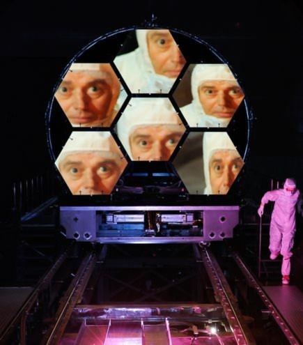 Hình ảnh khuôn mặt của giáo sư Mark Clampin phản chiếu trên những tấm kính của kính thiên văn vũ trụ James Webb được đặt tại Trung tâm vũ trụ Marshall ở Alabama.  Kính thiên văn có đường kính rộng 6,5m này được xây dựng để thay thế cho kính thiên văn Hubble. Dự kiến, kính thiên văn vũ trụ James Webb sẽ chính thức hoạt động vào năm 2014.
