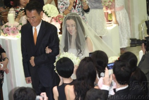 Phạm Vĩ Kỳ được người bố dắt đến bên cạnh chú rể. Cô dâu cười rất tươi sau làn voan mỏng.