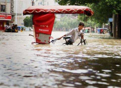 Một người đạp xe qua nước lụt ở thành phố Lan Tây, tỉnh Chiết Giang. Ảnh: AFP.