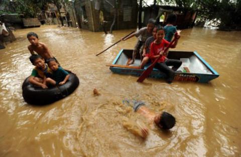 Giữa dòng nước đục ngầu trên phố, người ta đi lại bằng phao, xuồng tôn, hay thậm chí bơi.