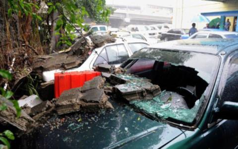 Những chiếc xe hơi bị hư hỏng do tường đổ đè vào, ở Manila.