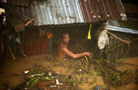 Một người đàn ông trước cửa căn nhà ngập ngang ngực. Rác rưởi đang chực theo dòng nước tràn vào trong.