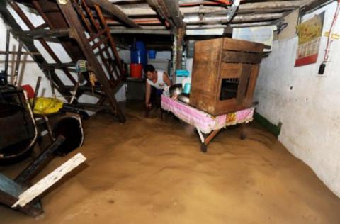 Bên trong căn nhà này, một người loay hoay tìm cách kê dọn đồ đạc tránh nước.