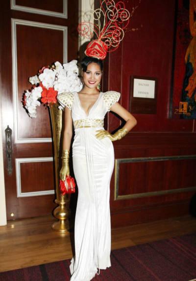 Bông hoa hồng trên đầu được điểm xuyến một cách khéo léo và tinh tế kết hợp với chiếc bóp cầm tay thể hiện phong cách sang trọng
