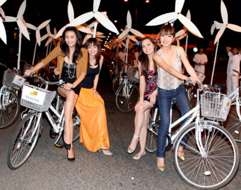 Hoàng Yến chở Trúc Diễm (trái) và Jennifer Phạm đèo Thúy Vy Victoria trên hai chiếc đạp đi vòng quanh phố khuya Nha Trang mùa lễ hội.