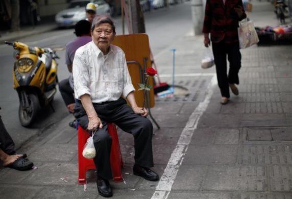 Hình ảnh một cụ già cầm bông hoa hồng ngồi trên vỉa hè ở Thượng Hải, Trung Quốc.