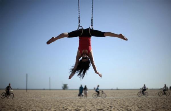 Một cô gái tập thể dục vòng treo trên một bãi biển ở Santa Monica, California, Mỹ.