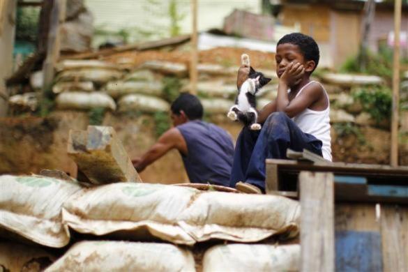 Một cậu bé đang chơi với mèo, trong khi, bố cậu bé đang dựng lại ngôi nhà sau trận lở đất ở Caracas, Venezuela.