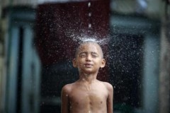 Ảnh ấn tượng: Chú tiểu thích thú tắm dưới mưa