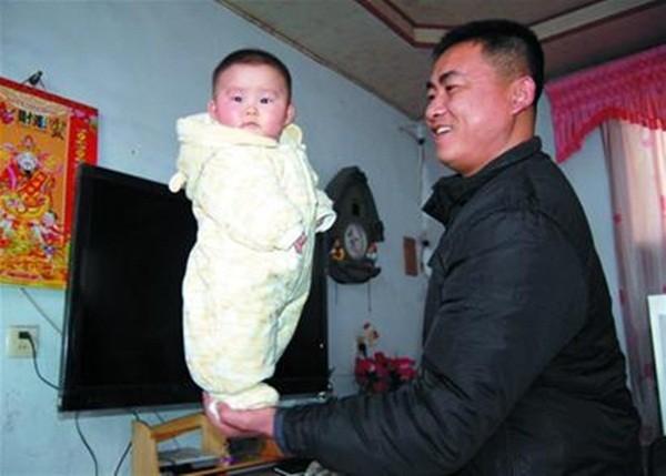 Bé gái 4 tháng tuổi đứng trên bàn tay bố.