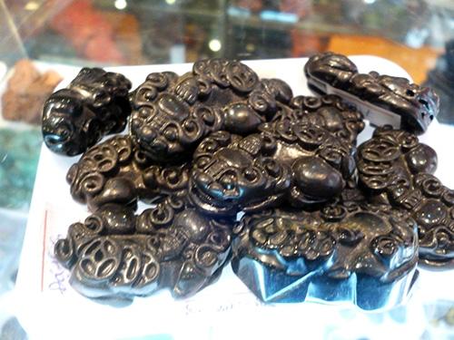"""Đá """"thiên thạch"""" Téc-tít (Tektite) tại cửa hàng ở phố Doãn Kế Thiện được chế tác thành linh vật phong thủy tì hưu."""