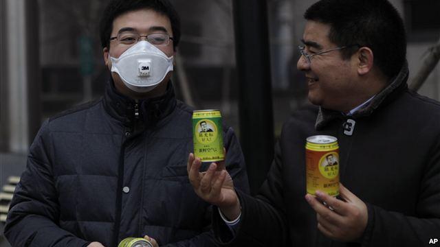 Doanh nhân triệu phú Trần Quang Tiêu (phải) đưa một lon không khí sạch cho một người đeo mặt nạ, đi trong trung tâm thủ đô Bắc Kinh, vào một ngày mù sương, 30/1/13