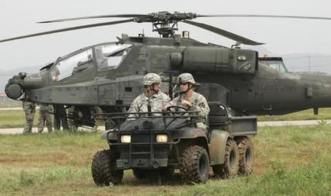 Các binh sĩ Mỹ đi trên thiết bị quân sự trước một chiếc trực thăng AH-64D Apache của Tiểu đoàn tấn công trên không số 4 thuộc Lữ đoàn tấn công trên không số 2 ở căn cứ không quân Mỹ tại Gunsan.