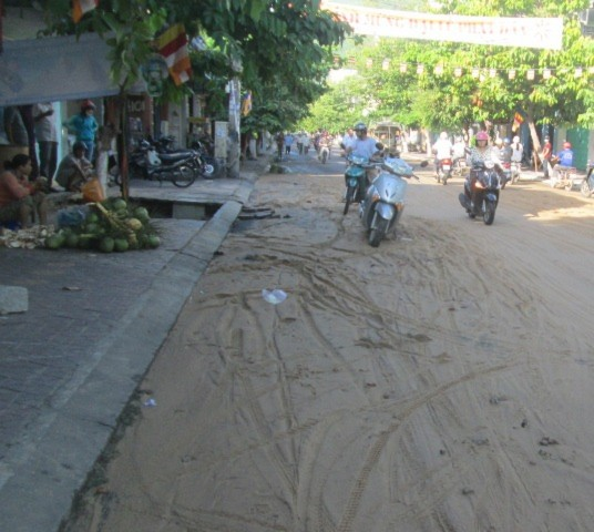 Đất cát tràn xuống lòng đường gây khó khăn cho người đi xe máy