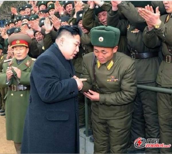 Một quân nhân vừa cúi rạp người vừa rớm lệ khi được nhà lãnh đạo bắt tay