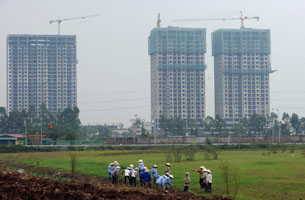 Công nhân dịch vụ môi trường đô thị làm việc gần một dự án bất động sản ở ngoại ô Hà Nội vào ngày 04 tháng 10 năm 2012. Ảnh minh họa. AFP photo