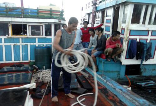 Thuyền trưởng Mai Văn Cường, đang cuốn lại bành dây neo bị chặt phá.