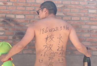 """Nhà văn Bắc Kinh, Vương Zang đặt trên bàn làm việc tại Bắc Kinh những dòng chữ Trung Quốc viết nguệch ngoạc trên lưng khi đang cầm một con thú bông và một chai rượu hôm 29/5/2013 """"Hiệu trưởng ơi, tìm một phòng [với em] đi. Hãy để những em học sinh nhỏ được yên."""" Những nghệ sĩ, những nhà hoạt động xã hội, sinh viên đại học và công chức cảnh sát đang tự chụp ảnh – một số khoả thân và tạo dáng khêu gợi, một số giận dữ và đe doạ - với cùng một thông điệp (AP Photo/Courtesy of Wang Zang)."""