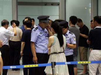 Cảnh sát và an ninh Trung Quốc đang thu thập thông tin tại cửa B, khu đến sân bay Quốc tế Bắc Kinh, sau vụ một người tàn tật cho nổ bom, 20/07/2013 REUTERS