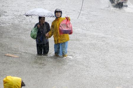 Một nhân viên Thoát nước Hà Nội giúp đỡ người dân vượt qua chỗ ngập sâu.