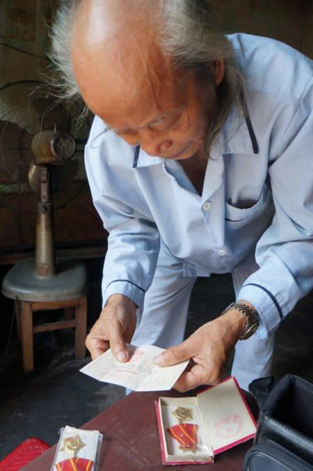 Cụ Hà Văn Ninh đang lục những hy hiệu Huân chương kháng chiến hạng Nhì mà Nhà nước phong tặng cho vợ chồng cụ vì có công.