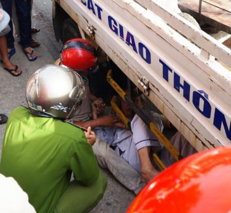 Cụ Ninh bức xúc chui vào gầm xe CSGT phản đối sự việc, được công an, người nhà vận động đưa cụ ra ngoài.