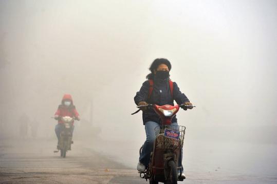 Ảnh chụp màn hình cho thấy người dân đi xe máy bịt khẩu trang trong một ngày khói bụi ở phía nam thành phố Nam Kinh Trung Quốc ngày 7 tháng 12
